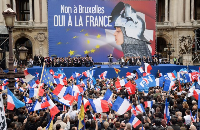 """Supporters of France's far-right National Front (FN) wave French flags as leader Marine Le Pen (rear C) delivers a speech in front of a poster depicting Joan of Arc (Jeanne d'Arc) and reading """"No to Brussels, yes to France"""" during a May Day rally in Paris on May 1, 2014. AFP PHOTO / PIERRE ANDRIEU (Photo credit should read PIERRE ANDRIEU/AFP/Getty Images)"""